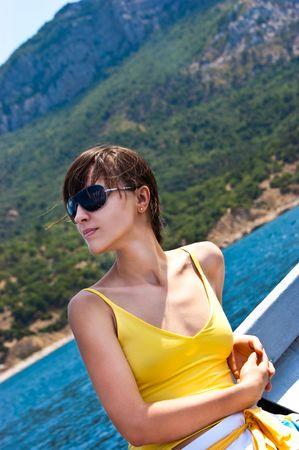 Pretty girl dreaming while sailing near the coastline Archivio Fotografico