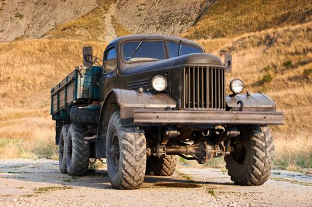 Abandoned old truck standing alone near the hill photo