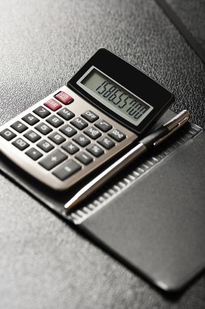 Close-up image of a calculator with a pen on a black background Archivio Fotografico