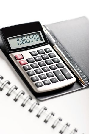 Close-up image of a calculator with a pen on a white background