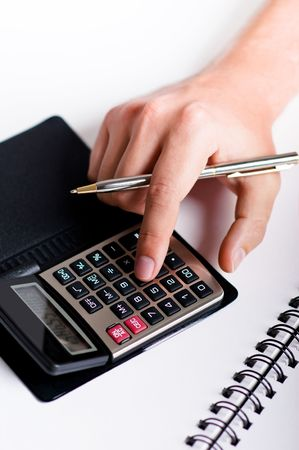 Hand with pen is typing numbers on calculator