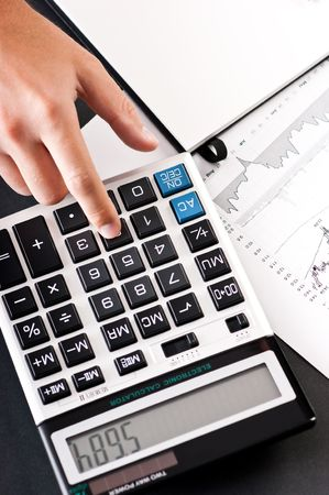 Close-up of hand using calculator with stock charts and notepad