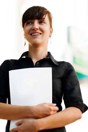 Attractive businesswoman with her arms crossed on a folder