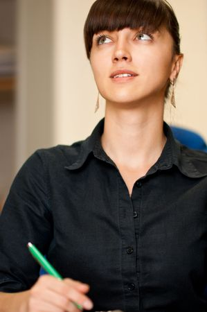 Attractive businesswoman with a pen in an office environment