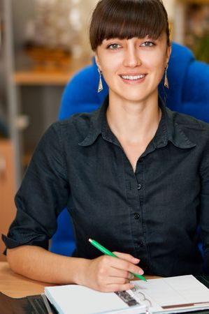 Attractive businesswoman writing in notebook in an office environment