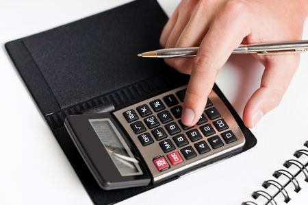 Close-up of a hand typing on calculator with a white background Archivio Fotografico