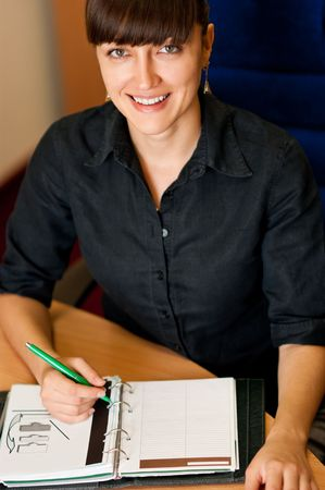 Smiling businesswoman with a pen looking at camera
