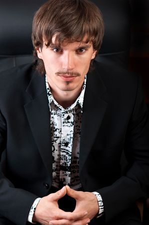 Portrait of serious young businessman looking at camera against black background