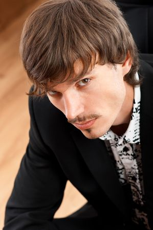 Portrait of serious young businessman looking at camera in office environment photo