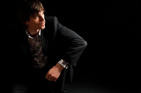 Portrait of stylish young businessman sitting on the flor with black background