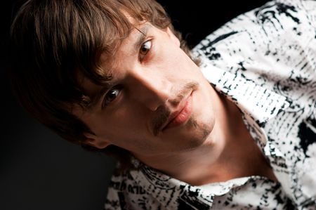 Portrait of stylish guy looking at camera against black background
