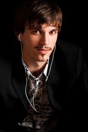 Young man enjoying music with headphones against black background