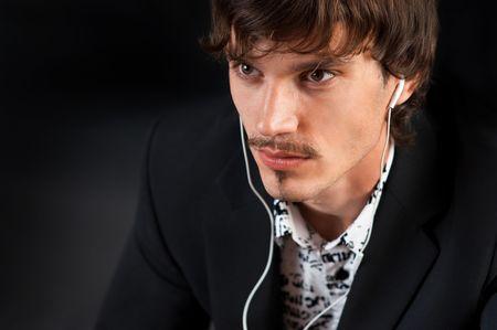 Stylish young man enjoying music wearing white headphones against black background Archivio Fotografico