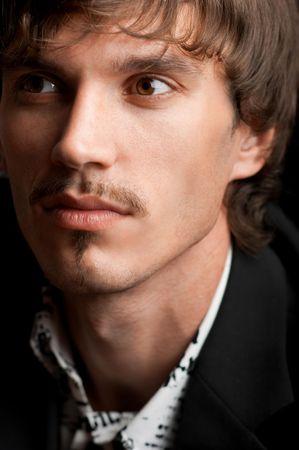 Portrait of stylish confident businessman against black background