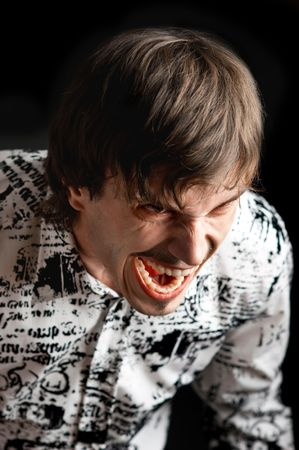 outraged: Portrait of a young man shouting with angry expression against black background Stock Photo