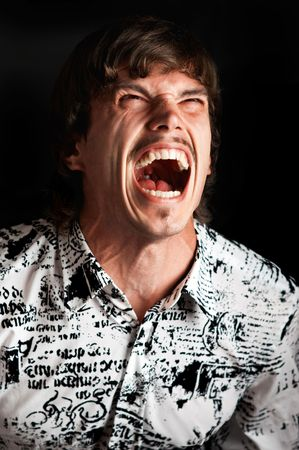 Portrait of a young man screaming out loud against black background