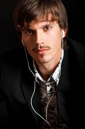 Serious stylish man listening to music against black background Archivio Fotografico
