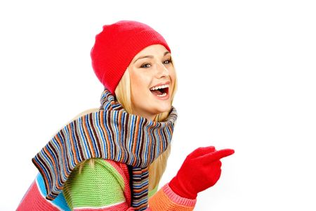 Photo of an attractive girl wearing winther clothes and pointing at something against white background