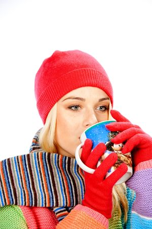 Teenage girl in winter clothes with cup of hot drink against white background