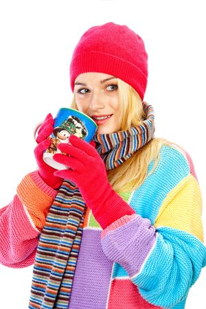 Portrait of pretty woman wearing warm clothes holding a cup against white background
