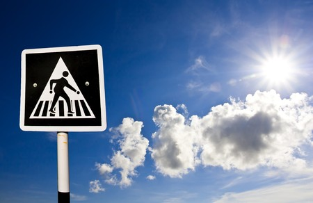 Pedestrian crossing traffic sign against  blue sky  photo