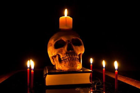 Halloween image with a burning candle and ancient skull on book  Stock Photo