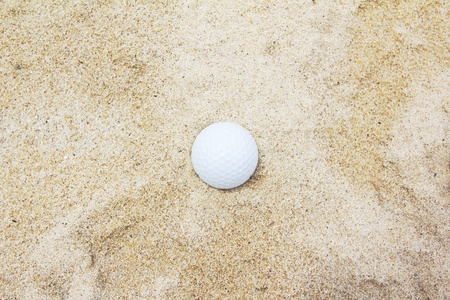White golf ball on sand