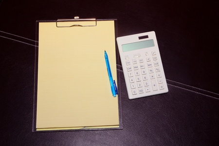 Clip board, Calculator pen on dark brown leather background photo