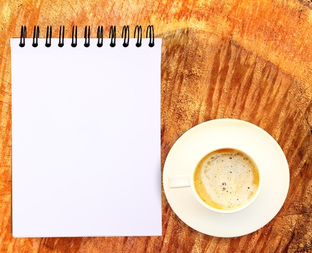 Blank paper tablet with coffee cup on wood background photo