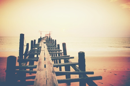 woody bay: Old wood bridge to the sea sunset  Stock Photo