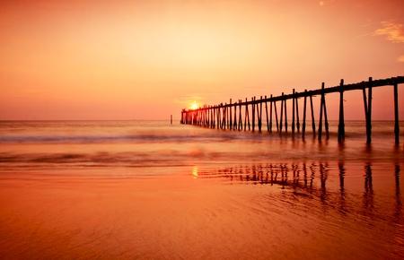 Mooie Zonsondergang en oude houten brug naar de zee Stockfoto