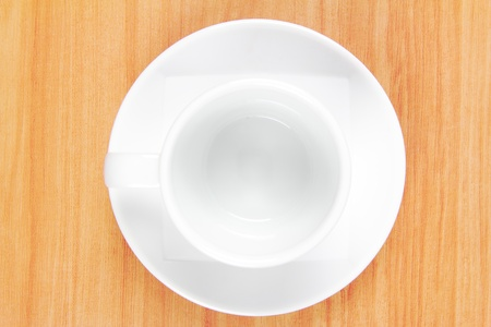 Empty white coffee cup on wood background photo