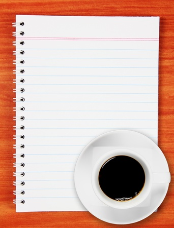 Blank notebook with black coffee on wood background photo
