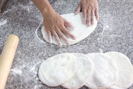 Human hands kneading bread dough for pizza photo