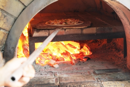 Chef placing fresh pizza in wood fire oven for baking in restaurant  Stock Photo