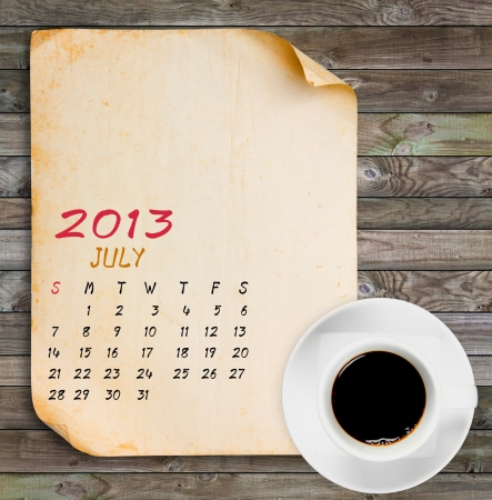 July 2013 Calendar, Vintage paper with Black coffee on wood panels background photo