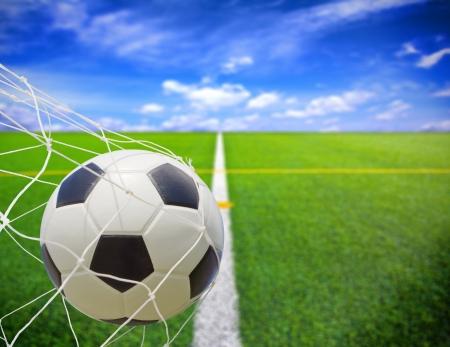 soccer ball in goal net over blue sky background photo