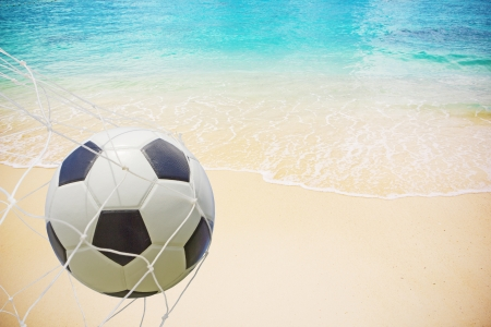 Soccer ball in a net on beach background