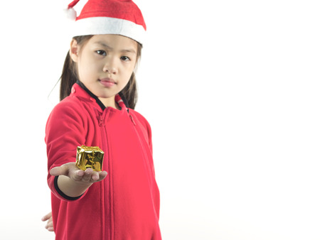 children s: Little girl in the santa claus hat, holding a gift box in hand