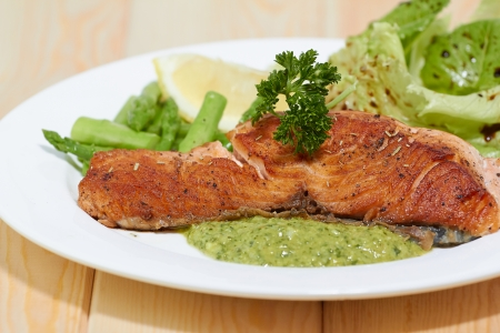 Grilled salmon steak with Salsa Verda sauce , lemon and vegetables photo