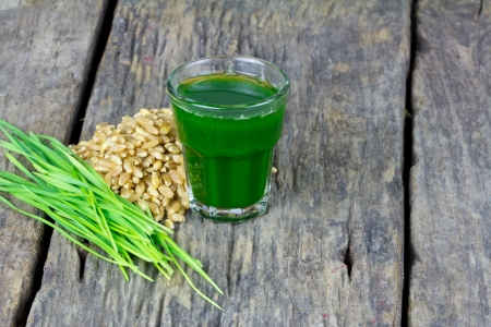 wheat grass: Wheat grass juice with fresh wheat grass and wheat on wood background