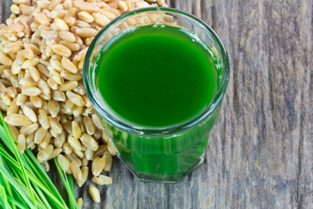 Wheat grass juice with seed and wheat on wood background