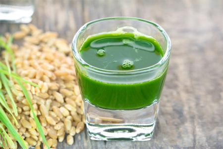 Wheat grass juice with fresh wheat grass and wheat on wood background