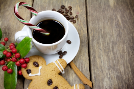 gingerbread man and a cup of coffee on old wood background  photo