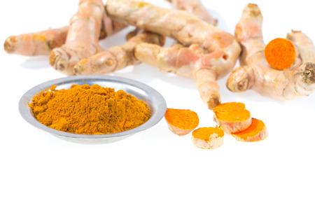 curcumin: turmeric powder with fresh turmeric root on white background