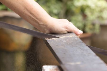 thatcher: carpenter worker sawing wood board with hand saw, close up hand