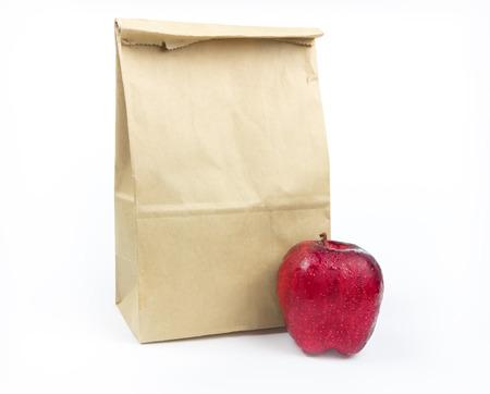 Bolsa de papel marrón del almuerzo con la manzana roja sobre fondo blanco Foto de archivo - 27817650