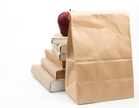 Fresh apple on stack of old books and lunch bag isolated on white photo