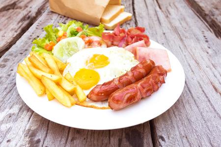huevos fritos: Desayuno americano con huevos fritos, tocino, salchichas, frijoles, tostadas y ensalada fresca en el fondo de madera vieja