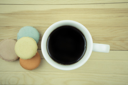 macaroons with coffee on wooden table view top photo